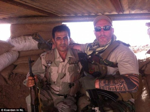 Defence: A biker from the No Surrender gang in the Netherlands, identified only as Ron (right) poses alongside a Kurdish soldier in Syria after going to fight against ISIS